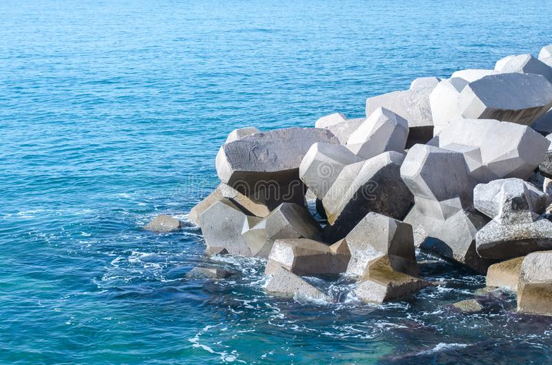 Concrete figure blocks thrown into the sea. Quay of Athens, Greece royalty free stock images