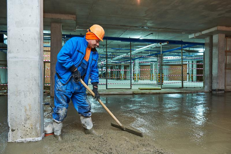Concrete floor construction. Worker with screeder stock photography