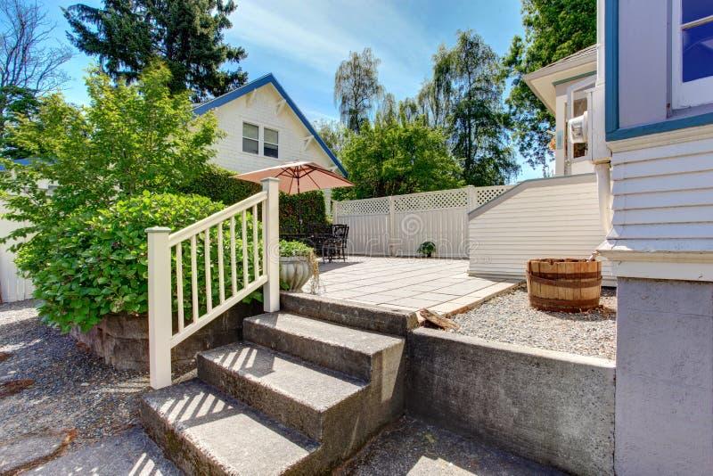 Concrete floor cozy patio area with iron table set and patio umbrella. royalty free stock photography