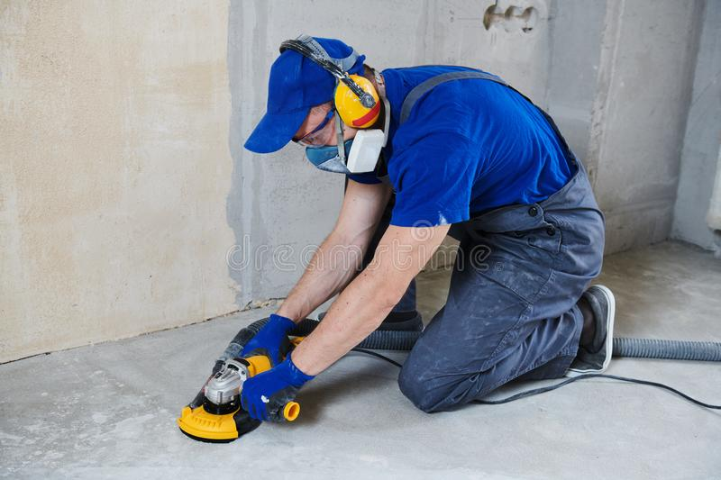 Concrete floor surface grinding by angle grinder machine stock images
