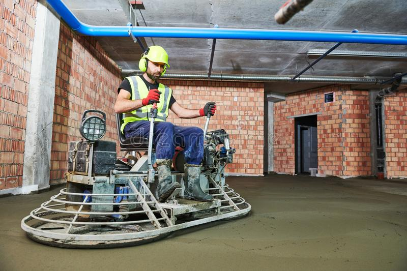 Concrete flooring. using ride-on power trowelling machine for surface floating stock images