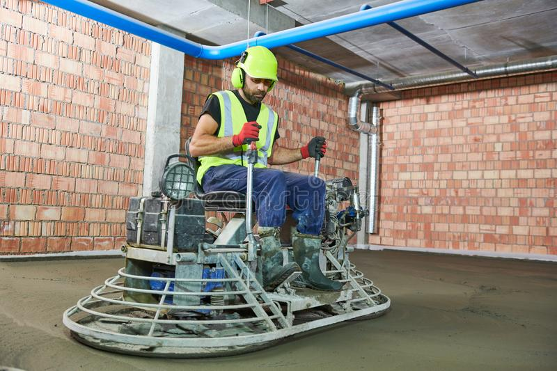 Concrete flooring. using ride-on power trowelling machine for surface floating stock photography