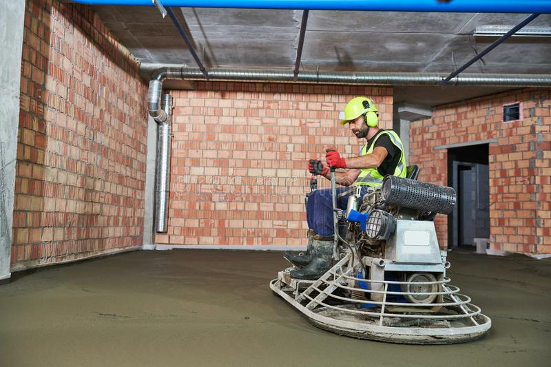 Concrete flooring. using ride-on power trowelling machine for surface floating stock photo