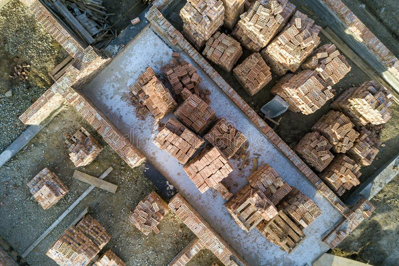 Concrete foundation of basement or first floor of future house with stacks of red bricks for walls construction on sunny summer. Day, aerial view stock image