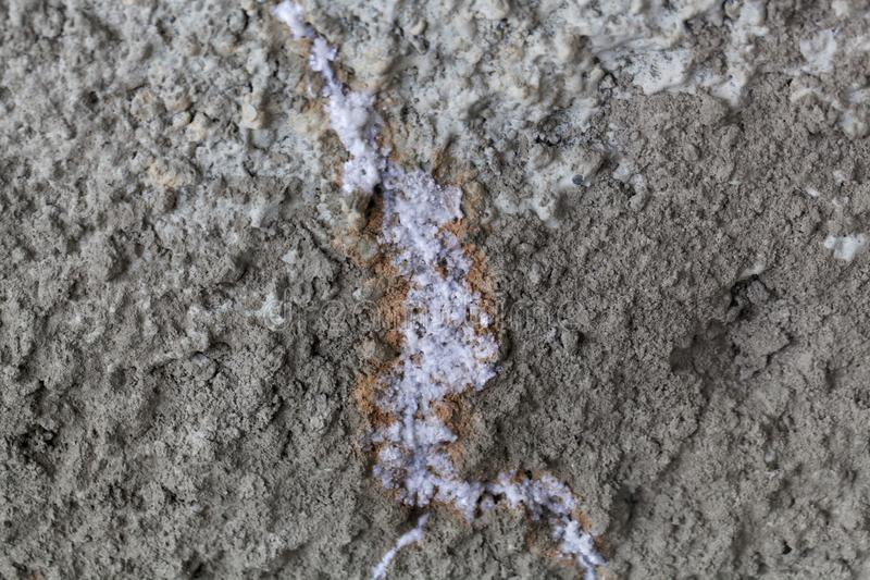 Concrete with a fracture and white carbonate crystallization stock photography
