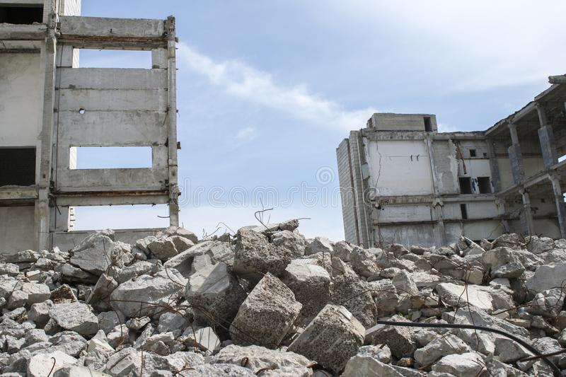 Concrete gray debris close-up on the background of the remains of the destroyed building against the sky. Background royalty free stock image
