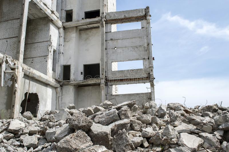 Concrete gray debris close-up on the background of the remains of the destroyed building against the sky. Background royalty free stock photo
