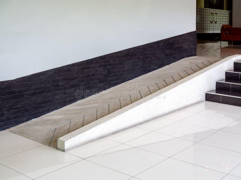 Concrete hellingsmanier voor de gehandicapten van de steunrolstoel binnen het gebouw stock foto's