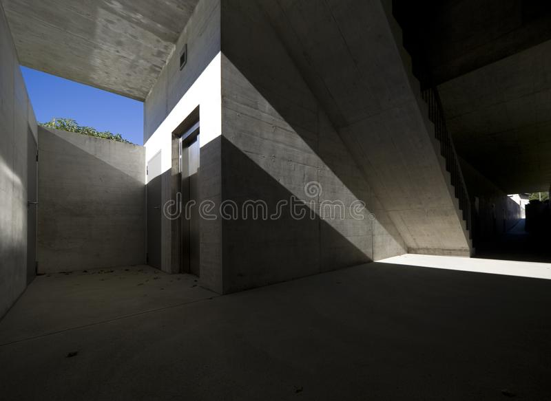 Concrete house underpass. Very strong cross shadow that gives character to the image. It is an exit of a lift that goes underground but the light still manages stock image