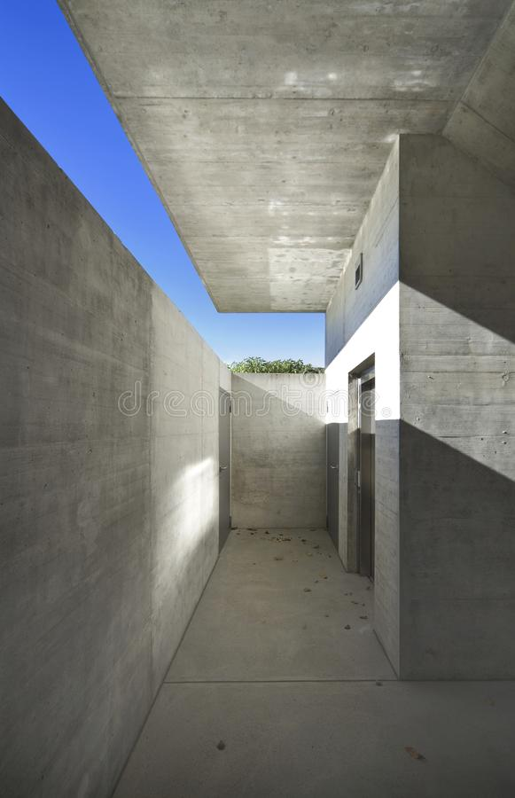 Concrete house underpass. Very strong cross shadow that gives character to the image. It is an exit of a lift that goes underground but the light still manages royalty free stock photos