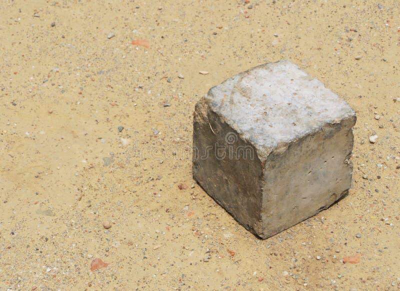 Concrete kubus die op zandgrond liggen die door slechte jonge geitjes wordt gebruikt om als stuk speelgoed met ruimte voor berich stock foto