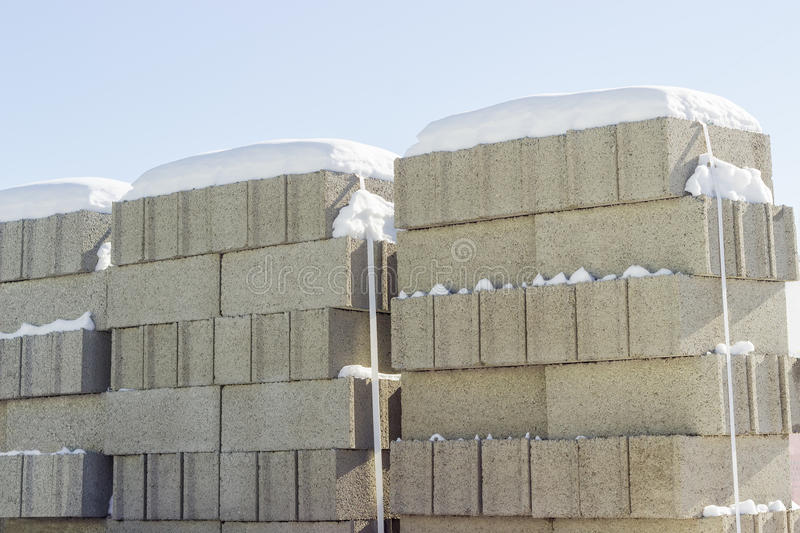Concrete masonry units closeup on an outdoor warehouse. Concrete masonry units packed on pallets and covered snow closeup on an outdoor warehouse in winter sunny stock photo