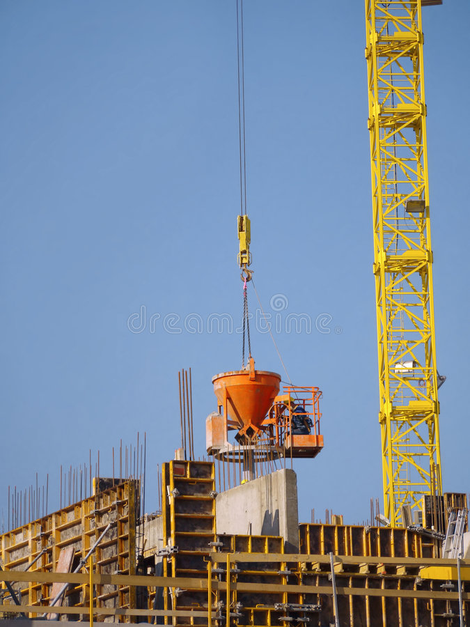 Concrete mix pouring. Construction worker pouring concrete mix from charging hopper transported by jib crane stock image