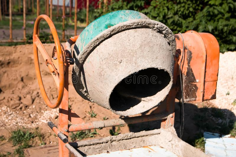 Concrete mixer against the sand, interfere with, concrete for construction royalty free stock images
