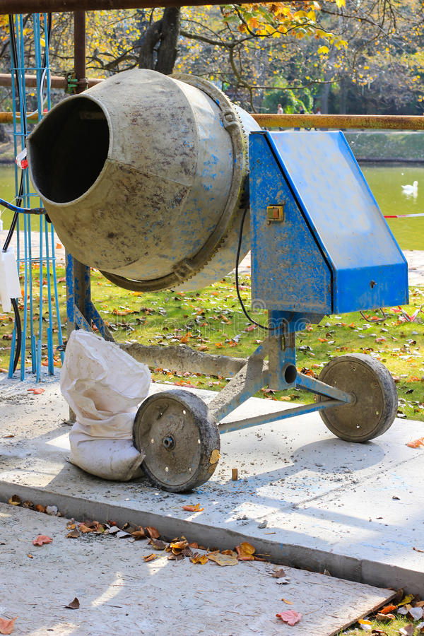 Concrete mixer and a bag of cement on the track. In the park royalty free stock photography