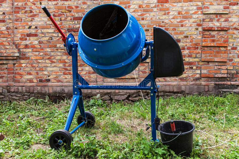 Concrete mixer. New blue cement mixer against a brick wall royalty free stock photos