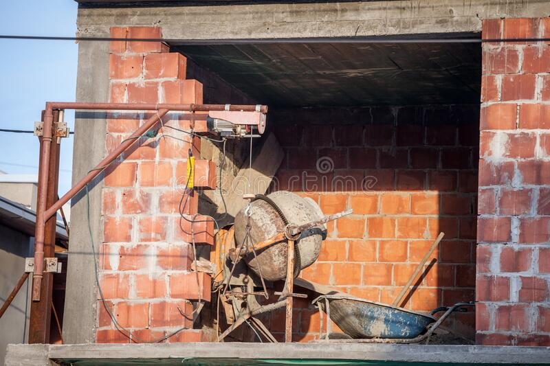 Concrete mixer ready for use on a construction site of a red brick house in a residential district of belgrade, serbia. stock photos