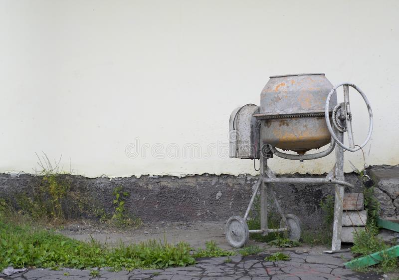 Concrete mixer to the wall. Concrete mixer stands at the wall on asphalt with grass stock photos