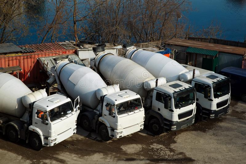Concrete mixers trucks and construction materials. On the parking near the river stock photo