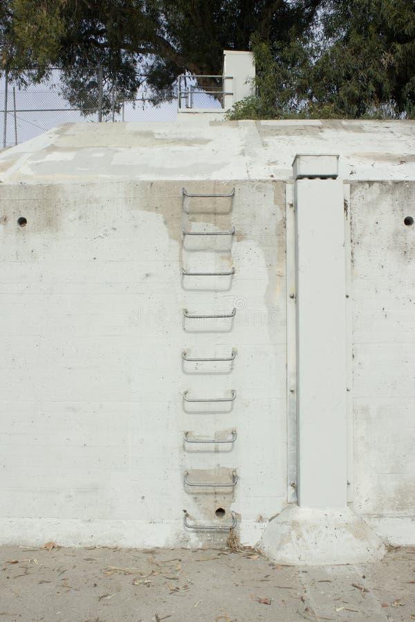 Concrete Muur met Afvoerkanalen en Metaal die Ladder beklimmen stock foto