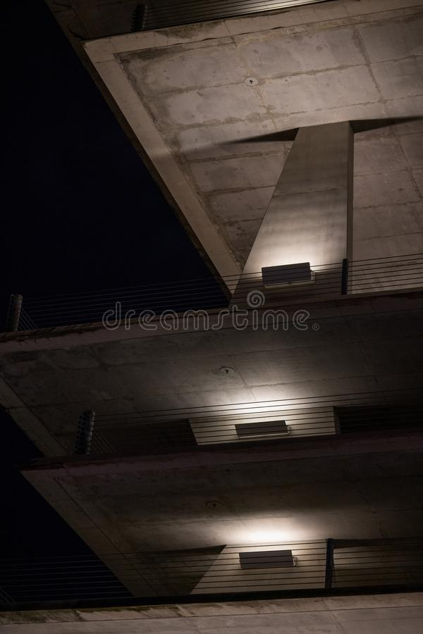 Concrete parking structure illuminated at night stock images