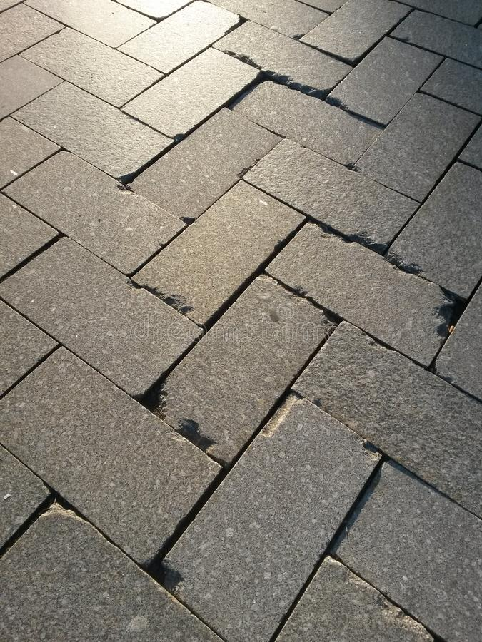 Concrete paving stones in the herringbone association with damage stock photography