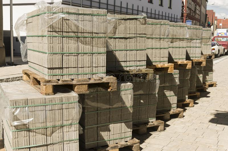 Concrete paving stones on wooden pallets at a road construction site in town. In germany royalty free stock photography