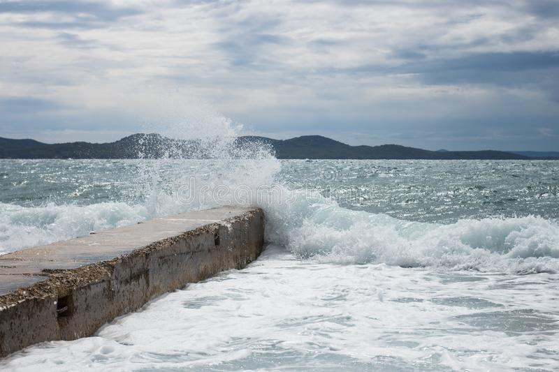 Concrete pier with a crashing wave in Zadar Croatia view at medieterranean sea royalty free stock photos