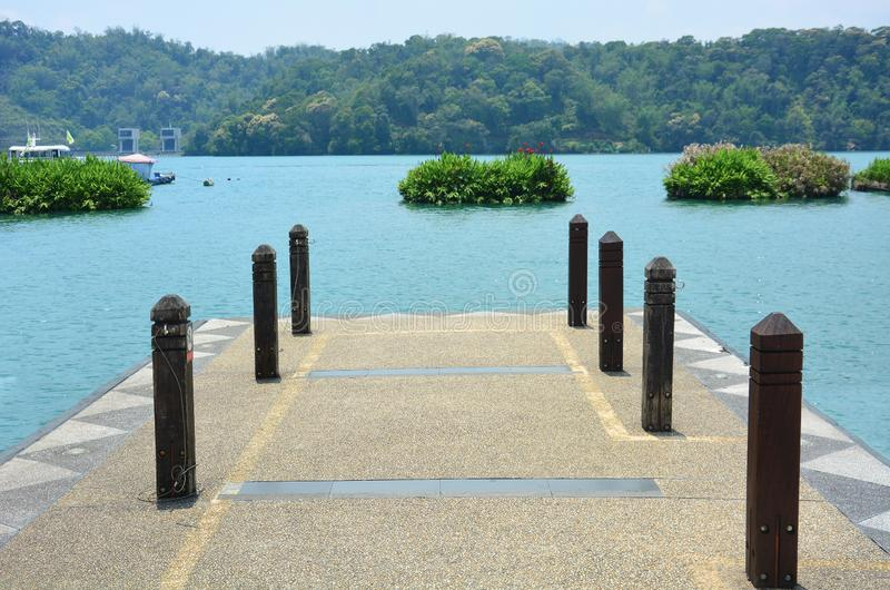 Concrete pier on the lake with mountain scenery background on a sunny day with turquoise water, sun moon lake, Taiwan stock photography