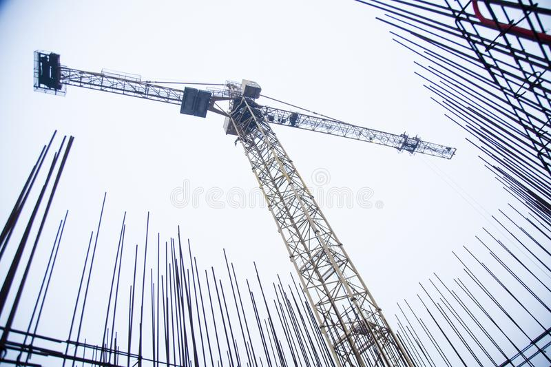 Concrete pillars on industrial construction site. Building of skyscraper with crane, tools and reinforced steel bars royalty free stock images