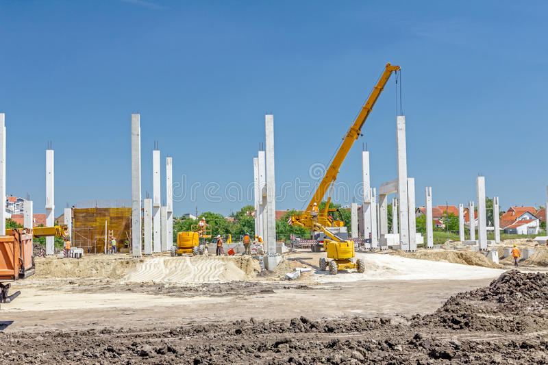 Concrete pillars of new edifice on sandy ground. Mobile crane is operating to assembly concrete skeleton of new edifice, mechanization working royalty free stock photos