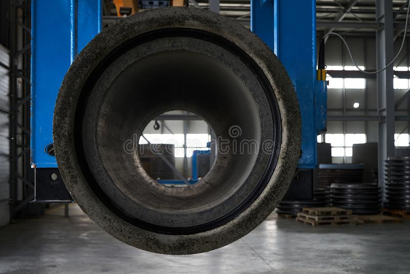 Concrete pipe on crane in factory warehouse. Industrial production of cement products concept royalty free stock images