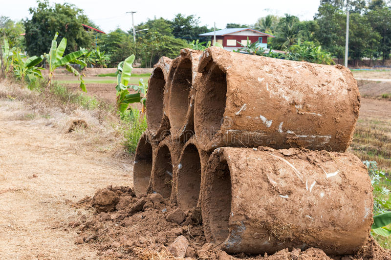 Concrete pipes with housing. Concrete pipe piles, which contaminated mud was left on the ground near a residential house royalty free stock images