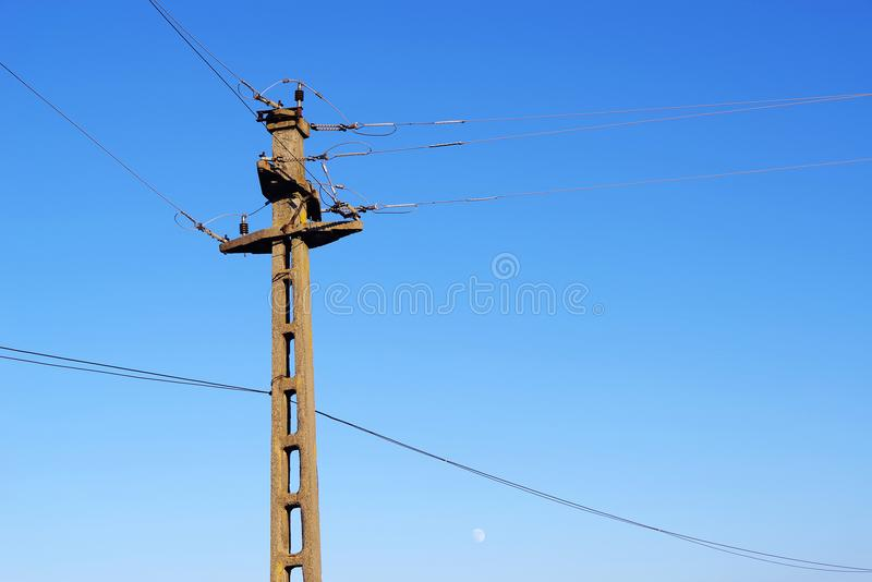 Concrete pole for aerial power lines against blue sky. The concrete poles are used like support for the conductors in transmission and distribution of the stock photo