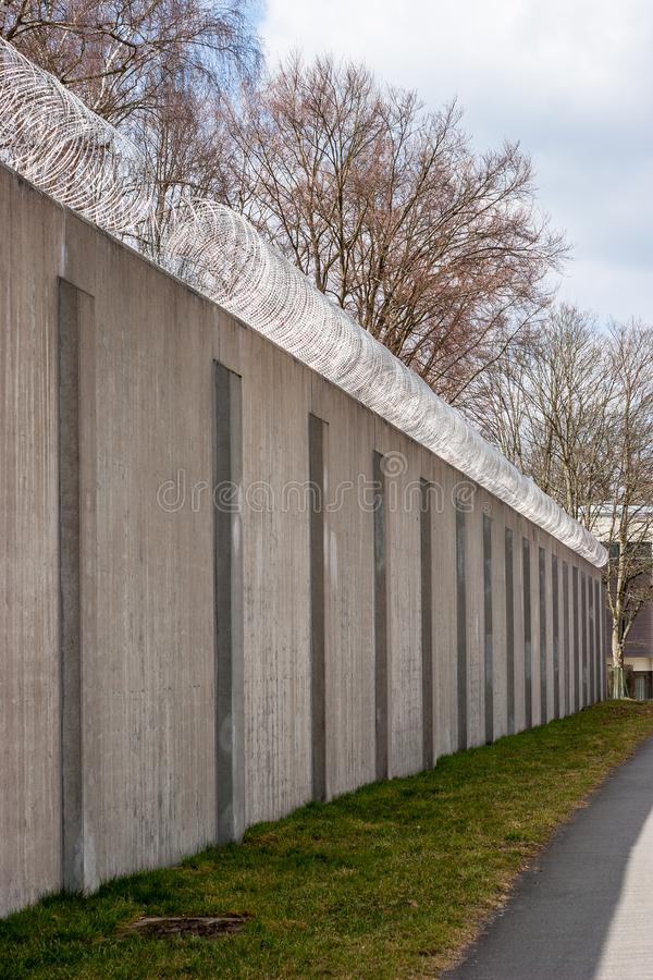 Concrete prison wall with surveillance camera. And barbed wire stock image