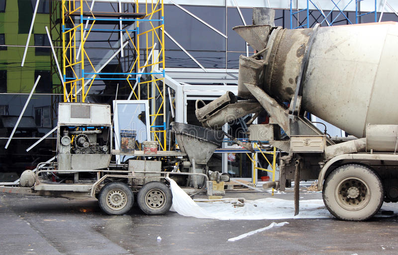 Concrete pump and mixer to work together pouring cement floors in the shopping center for repair. Concrete pump and concrete mixer to work together to pouring stock image