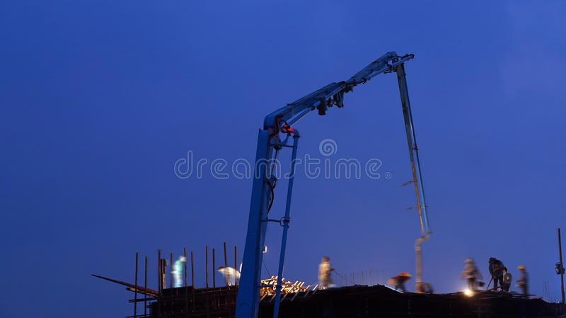 Concrete pump working at night royalty free stock photo
