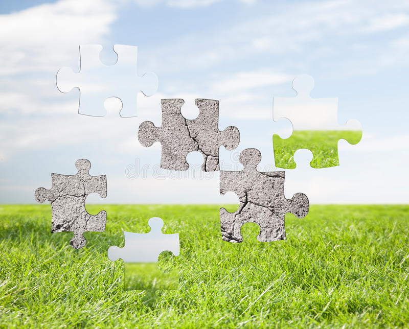 Concrete puzzle over blue sky and grass background stock photos