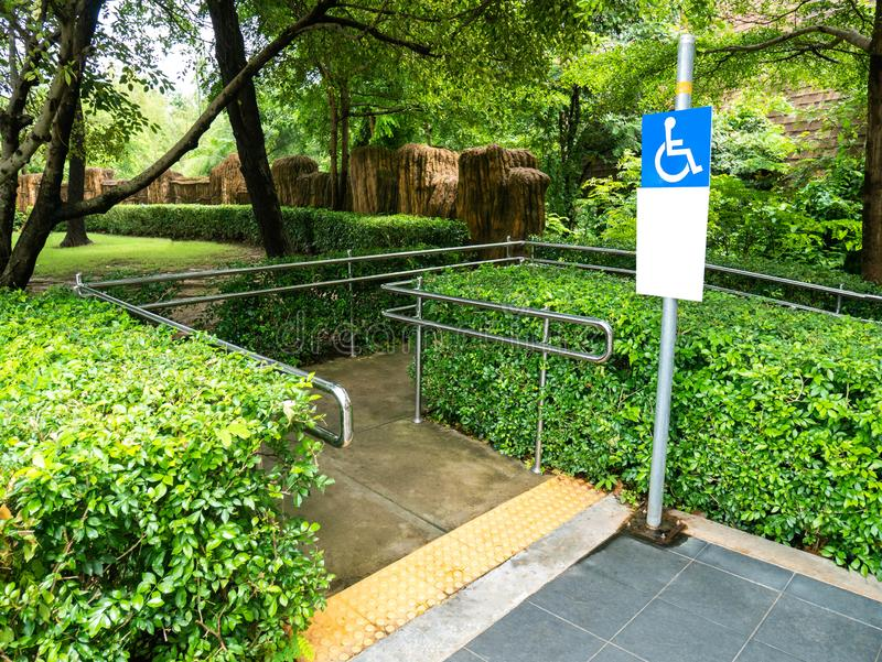Concrete ramp way with stainless steel handrail and disabled sign for support wheelchair disabled people in the park.  stock photos