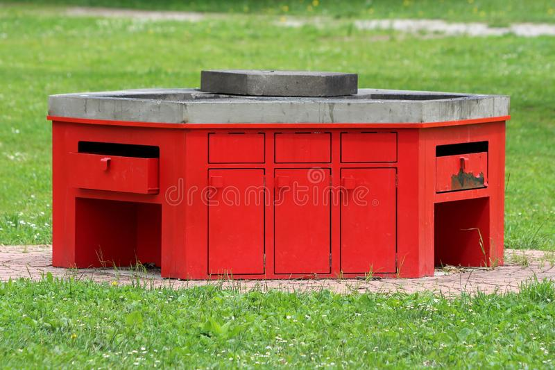 Concrete and red metal open public barbecue for public use in local park surrounded with stone tiles and uncut grass stock image
