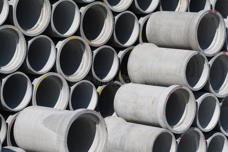 Concrete round pipes warehouse. Concrete round big pipes stacked in warehouse stock photo