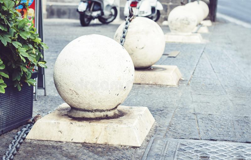 Concrete spheres prohibiting parking barrier on the street in Catania, Sicily, Italy.  stock photos
