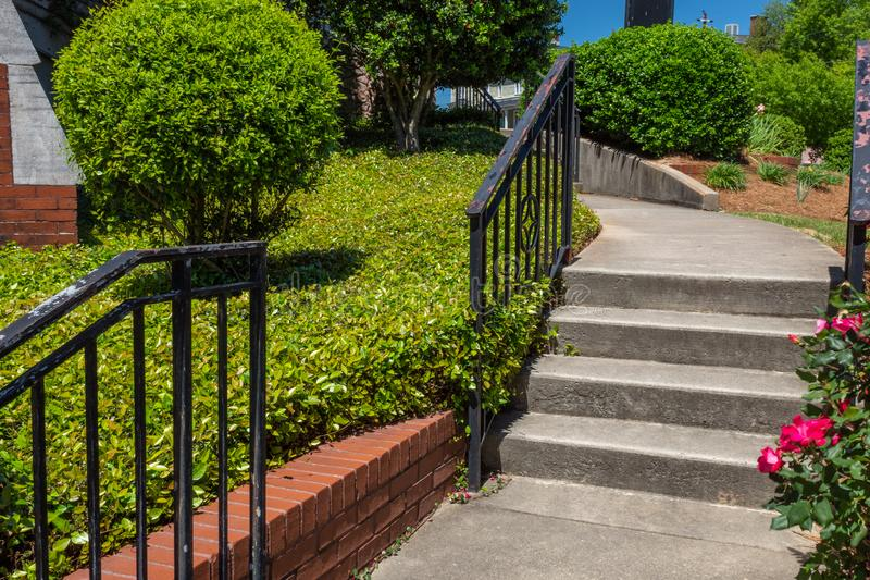 Concrete stairs and curving walkway bordered by brick retaining wall and groundcover stock photos