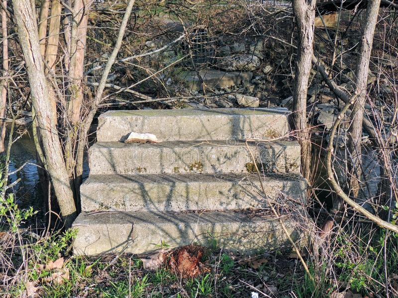 Concrete steps going to nowhere, ruins by river close to Bean Creek Garfield Park in Indianapolis Indiana USA. stock photos