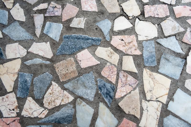 Concrete surface with multiple patches of colored stones royalty free stock photos