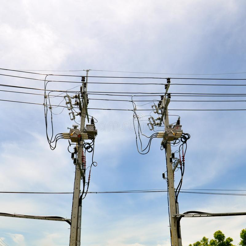 Telegraph poles and wires against a blue sky background. Concrete telegraph poles with many cables and conductors against a bright blue sky background stock photos