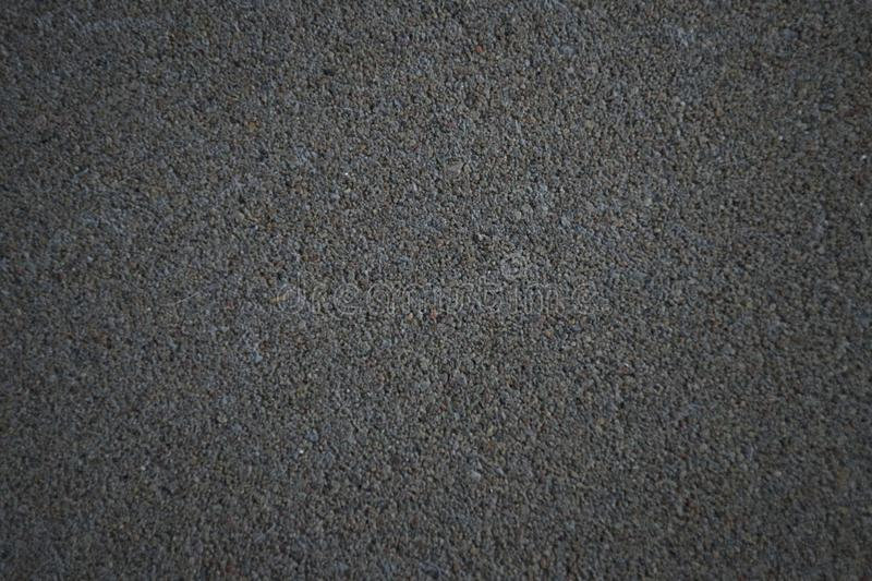 Concrete texture with blurred edges. Horizontal background of dark gray concrete floor with many small stones royalty free stock image