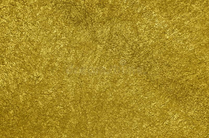 Concrete wall airbrushed with glossy golden paint. Rough texture of the concrete wall airbrushed with glossy graffiti paint of golden color. Background royalty free stock images