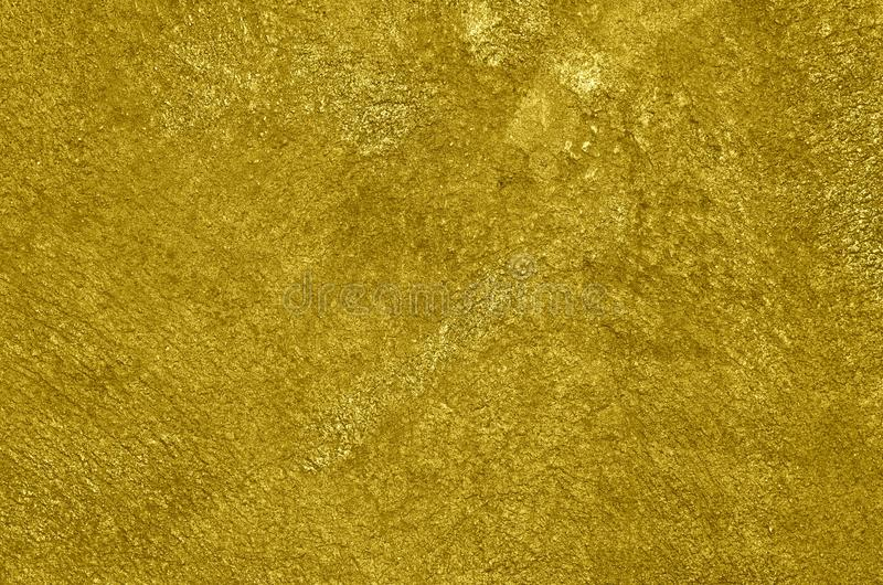 Concrete wall airbrushed with golden paint. Rough texture of the concrete wall airbrushed with graffiti paint of glossy golden color. Background stock images