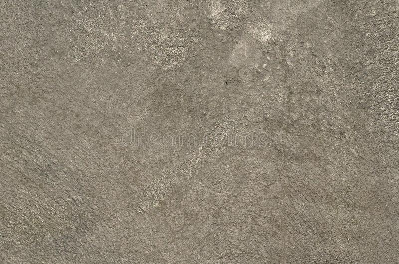 Concrete wall airbrushed with silver paint. Rough texture of the concrete wall airbrushed with graffiti paint of silver color. Background royalty free stock image